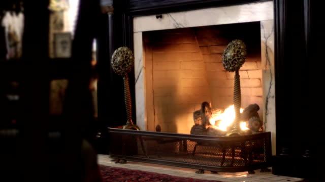 Medium Establishing shot of lit victorian fireplace in mansion living room video