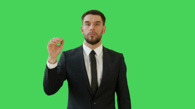 Medium Shot of a Businessman Making Swiping and Touching Gestures while Standing on a Green Screen Background. video