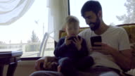 Medium shot of young boy and man playing on their cell phones video