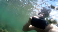 Medium view man wearing VR headset & swimming underwater in shallow tropical ocean tidepool video
