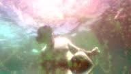 Medium wide shot Man descends under ocean waves wearing VR virtual reality headset - includes FX video