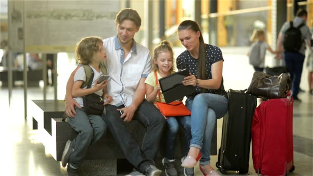 Members of a big family are watching photos from the vacation in tablet PC while sitting in waiting room of airport or railway station video