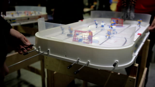 Men actively playing table hockey game at tablegames competition, wants to win video