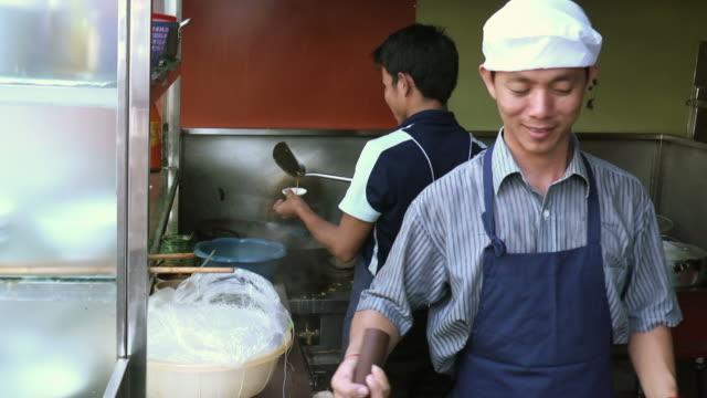 Men cooking as team in Asian restaurant kitchen video