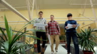 Men dressed in checkered shirts walk through shopping mall video