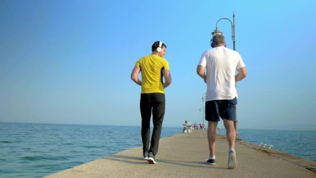 Men exercising by walking backward along the pier video