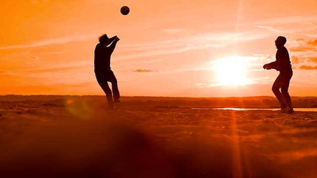 men fall to the sand behind the ball slow motion video video