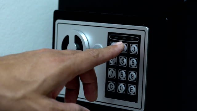 Men hands unlocking combination to safe in the hotel room video
