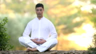 Men in meditating position outdoors video