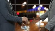 Men in suits shake hands. video