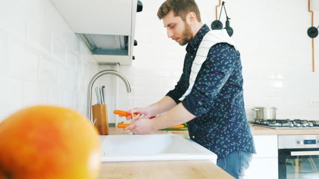 Men in the kitchen washing vegetables. video