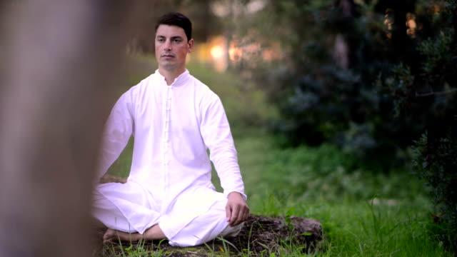 men in white clothing doing meditation in the park video