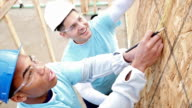 Men measure and mark plywood for house being built for charity video