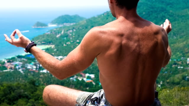 Men meditating on the top of an viewpoint in direction to Sairee Beach and Nang Yuan Island in Background video