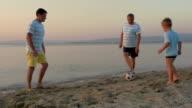 Men of three generations playing football on beach video