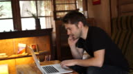 Men of young Caucasians to work with the net in a cafe video