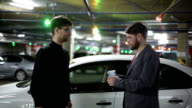 Men pass each other money and shake hands. Bokeh background video