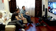 Men playing video game and girl using cell phone video