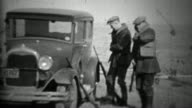 1933: Men preparing hunting shotguns at Ford model A car. video