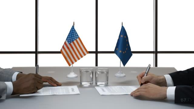 Men signing papers at desk. video