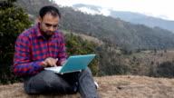 Men Sitting in Mountains Holding Laptop video