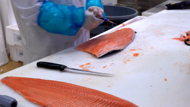 Men slicing a fillet of salmon at table in a fish shop. Dolly shot video