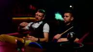 men smoke from shisha pipei n the lounge caffee. Slow motion video