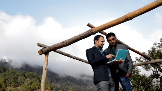 Men Standing in Mountains Holding Laptop video