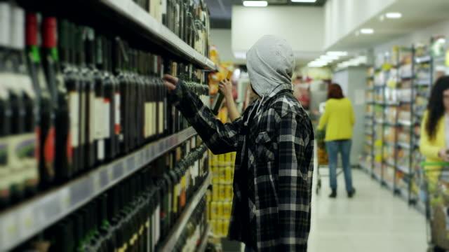 Men stealing wine bottle in supermarket video
