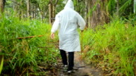 men that swear raincoat walk on wooded path video