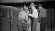 1935: Men tie dead hunted deer to front of Plymouth car for transport. video