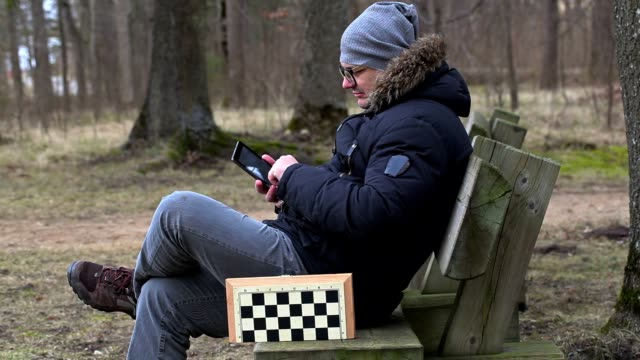Men using tablet PC in the park on bench video