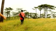 men walk pass through dry grass on top of mountain video