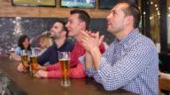 Men watching football at a sports bar video