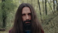 Men with solemn face and long hair standing in forest video