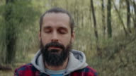 Men with solemn face standing in forest video