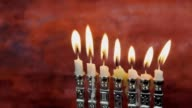 Menorah with candles over donuts on wood deck for Hanukkah celebration video