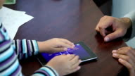 Men's and children's hands play on the tablet video