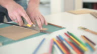 Men's hands cut off with a ruler and knife, brown paper on table with colored pencils video