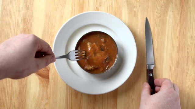 Men's hands get a sprat in tomato sauce from a tin can video