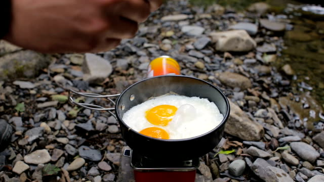 Men's hands salt fried eggs in a frying pan in a camping video