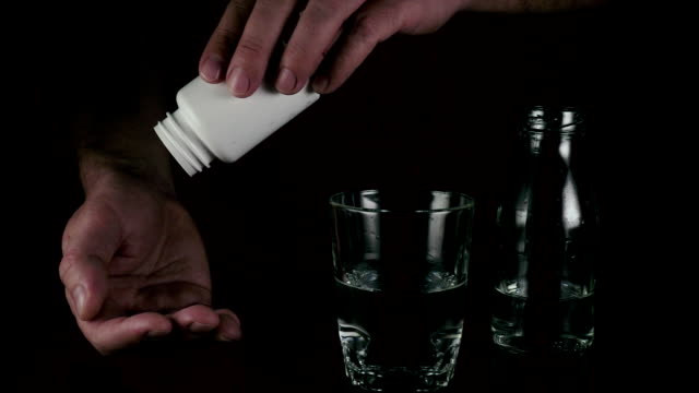 Men's hands shake the pill from the jar. Slow motion video