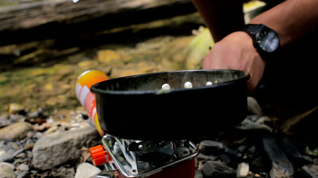 Men's hands stir fried eggs in a frying pan in a camping on a camp stoves video