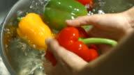 Men's hands washing bell pepper. video