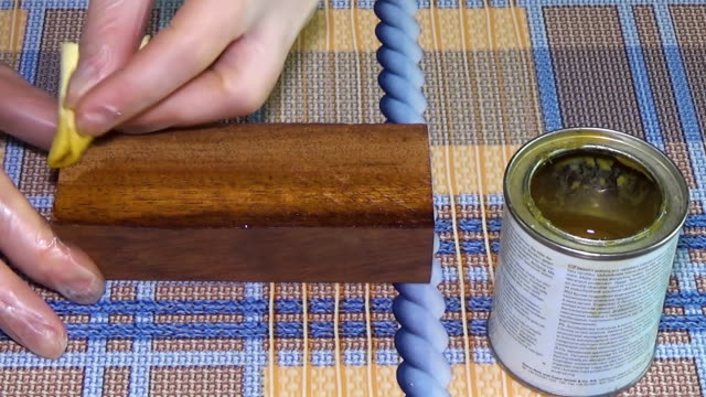 Meranti wood. The bar of solid wood is covered with stain. The girl covers a bar of rare wood with lacquer. The joinery impregnates the wood with wax. Checkered background video