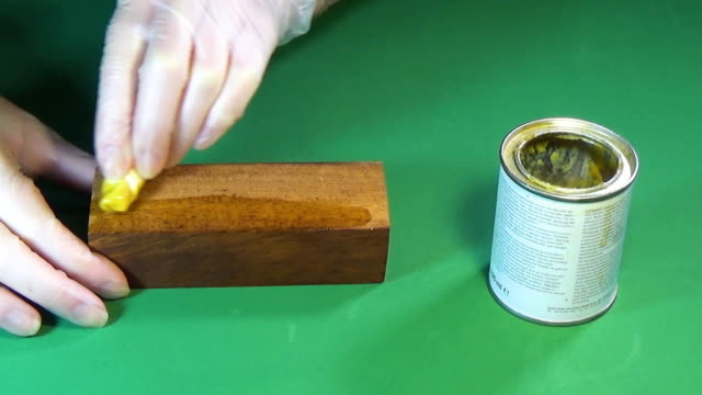 Meranti wood. The bar of solid wood is covered with stain. The girl covers a bar of rare wood with lacquer. The joinery impregnates the wood with wax. Chroma key video