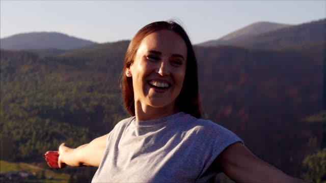 Merry woman outstretching hands at sunset in mountains video