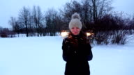 Merry woman with two bengal lights pose at snowbound park, slow motion shot video