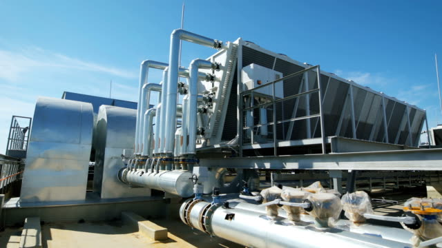 Metal chrome pipes are connected to a common water supply system for the enterprise. On the roof of an industrial building organized piping and ventilation video