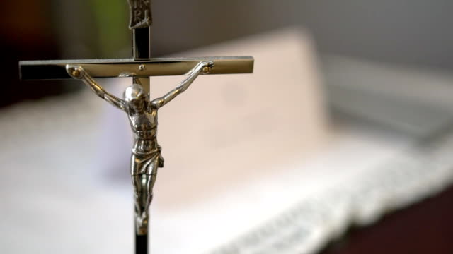 Metal Crucifix with Holy Bible Blurred in Background video